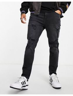 tapered jeans in washed black with heavy rips